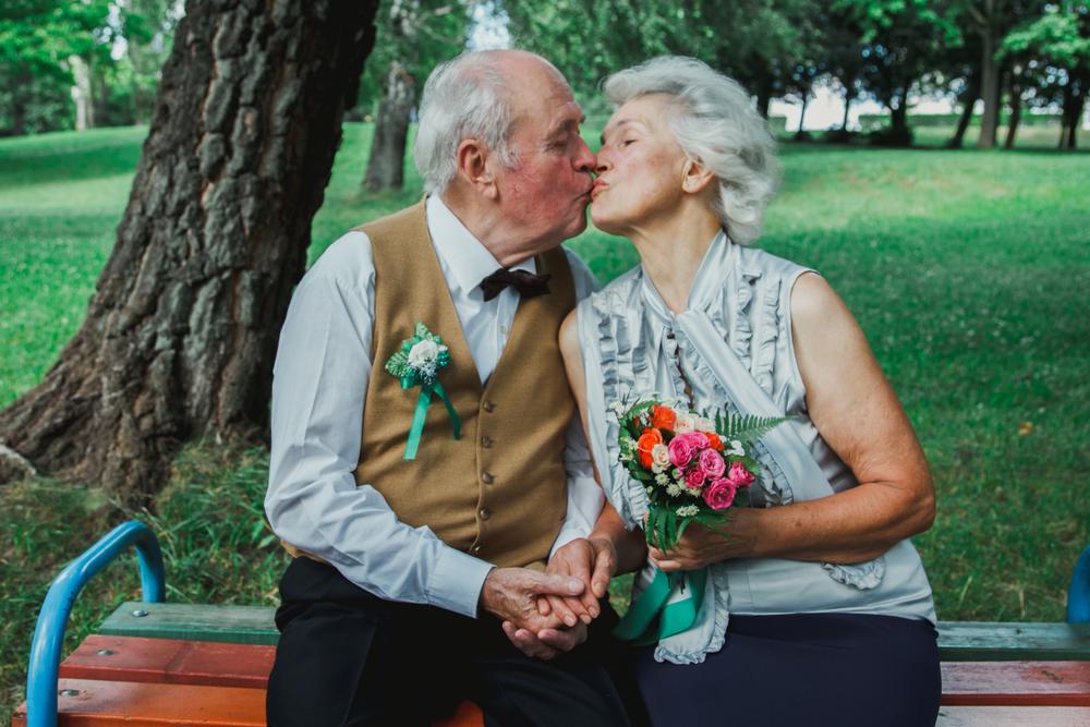 Älteres Ehepaar sitzt auf Parkbank und küsst sich