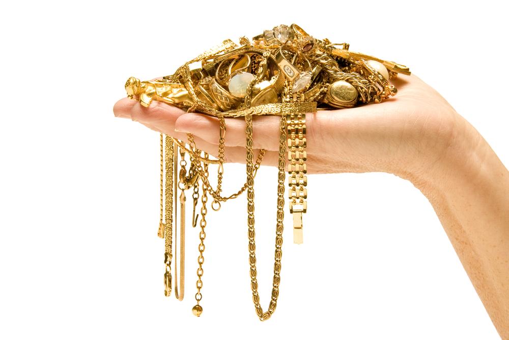 Eine Hand hält einen Haufen Goldschmuck so, als würde die Hand den Schmuck wiegen.