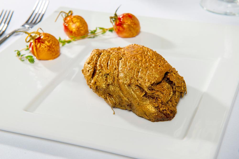 Kalbfleisch mit Blattgold-Ummantelung auf weißem Teller angerichtet