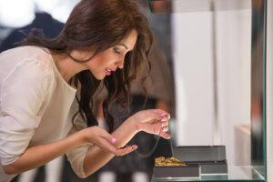 Junge Frau betrachtet eine filigrane Kette in einem Juweliergeschäft.