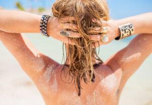 Blonde Frau, die sich die Haare hochhält. Sie trägt Ringe und Armreifen.