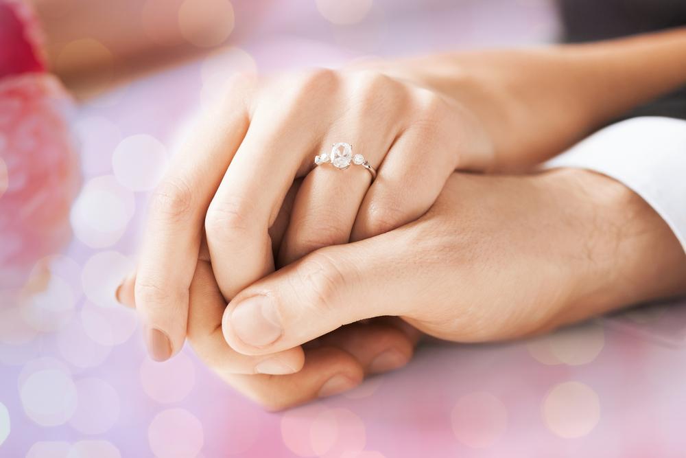 Ehepaar reicht sich die Hände, Frau trägt Diamantring