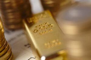 Goldbarren neben Geldmünzen und Aktiengraph