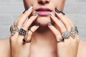 Die Hände einer Frau sind mit vielen üppigen Rigen und Nagellack geschmückt